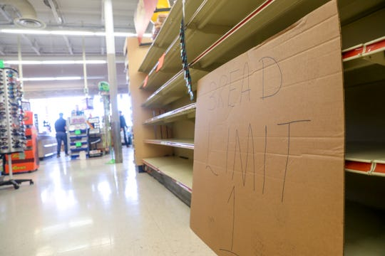 A large cardboard sign asks customers to limit their purchases to one item of bread at a time front of the nearly empty shelves at Hilltop Supermarket in Clarksville, Tenn., on Wednesday, March 25, 2020.