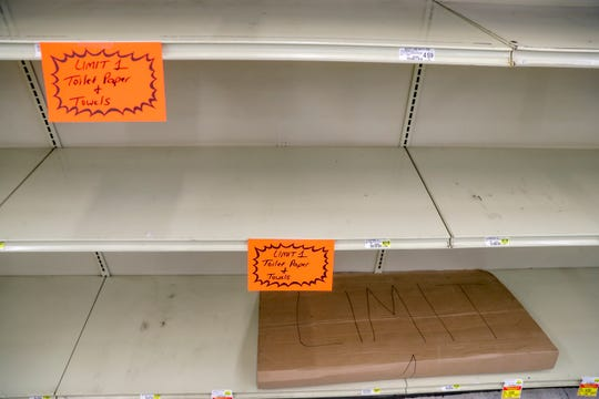 A large cardboard sign asking customers limit their purchase to one item is folded up on an empty shelf at Hilltop Supermarket in Clarksville, Tenn., on Wednesday, March 25, 2020.
