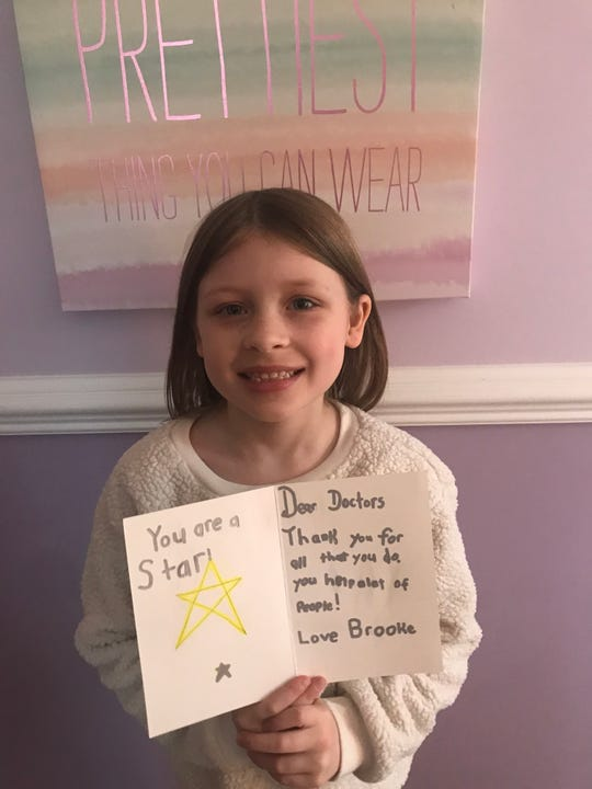 Warren's Grade 1 Central School student Brooke Thomasey shows off her finished thank-you card she made for the nurses and doctors at University Hospital in Newark.