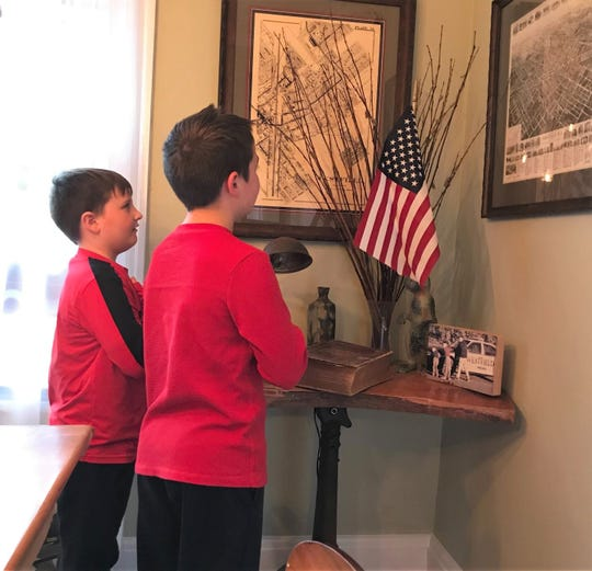McKinley first grader Gavin Reynolds (left) and his brother, third grader Dylan, participate in an at-home flag salute, illustrating the importance of school rituals and routines during distance learning.