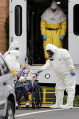 Residents from St. Joseph's Senior Home are helped on to buses in Woodbridge, N.J., Wednesday, March 25, 2020. More than 90 residents of the nursing home in Woodbridge are being transferred to a facility in Whippany after 24 tested positive for COVID-19, according to a spokeswoman for CareOne, which operates the Whippany facility. The facility has moved its residents to other facilities to accommodate the new arrivals.