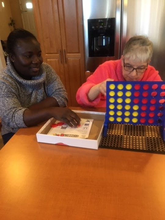At NJID Residential Services, a group home in Edison, NJID staff member Mary Amoakowah and resident Kathy challenges each other in a board game.