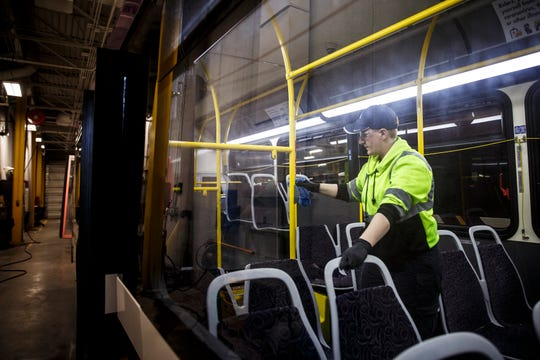 Erin Stanley, of Des Moines wipes down surfaces in a DART bus after they were sprayed with sanitizer on March 26 in Des Moines. DART regularly clean its 150 buses but has ramped up the cleanings with peak buses getting disinfected twice a day.