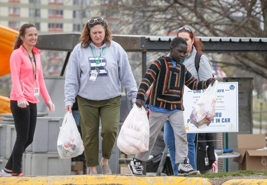Jessica Schmitt, left, and Monica Congdon of the Des Moines Public Schools hand lunch bags to a young student at the Oakridge Apartments on Thursday, March 26, 2020, as members of the DMPS prepared and handed out roughly 5,000 lunches.