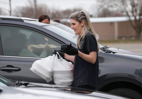 Lindsey Stewart of Bondurant brings food to a customer in their vehicle during curbside pickup at the Brick and Ivy Rooftop Restaurant in Altoona on Thursday, March 26, 2020.