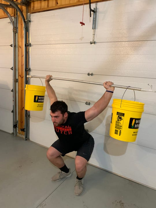 Central College junior linebacker Cade Humphries works out in his garage in Geneseo, Illinois.