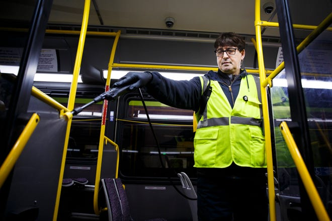 """Rafet Miftari of Des Moines, sprays sanitizer as he cleans a DART bus on Thursday, March 26, 2020, in Des Moines. DART regularly cleans their 150 buses but has ramped up the cleanings with peak buses getting disinfected twice a day. """"We are always looking for ways to do it better,"""" said Maintenance Supervisor Lyle Maberry adding that as the number of COVID-19 cases rose they ramped up their efforts and will continue to do so to keep the fleet running."""