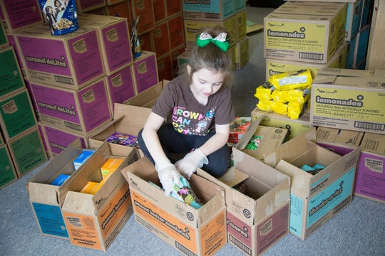 Carlisle Girl Scout Abby Hugen, 8, packs cases of cookies to donate and distribute. Carlisle Girl Scouts is holding a donation drive to give cookies to essential workers.
