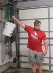 Central College junior offensive lineman Josh Mayhew works out in his parents' garage at their home in Aurora, Illinois.