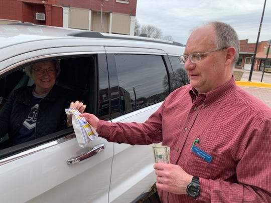 Mary Lou Klassen of Bedford.picks up a prescription outside Bedford Drug from pharmacist Mike Schweitzer. Schweitzer says he has a limited supply of drugs some are touting for COVID-19 treatment, and needs them for patients who have other conditions for which they're prescribed.