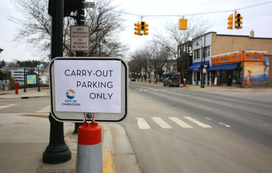 As non-essential businesses close throughout the state, the Northern Michigan town of Charlevoix had quiet streets, with parking spaces reserved for carry-out customers of area businesses.