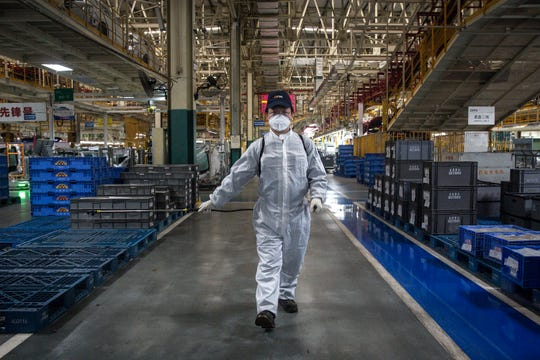 An employee wear sprays disinfectant along the assembly line at the Dongfeng Fengshen plant on March 24, 2020 in Wuhan, Hubei province, China. Wuhan has allowed car producers and auto part suppliers to resume work recently. The Dongfeng Passenger Vehicle Company has resumed production following epidemic prevention and control rules. Local media have reported that Wuhan will lift the lockdown on April 8.