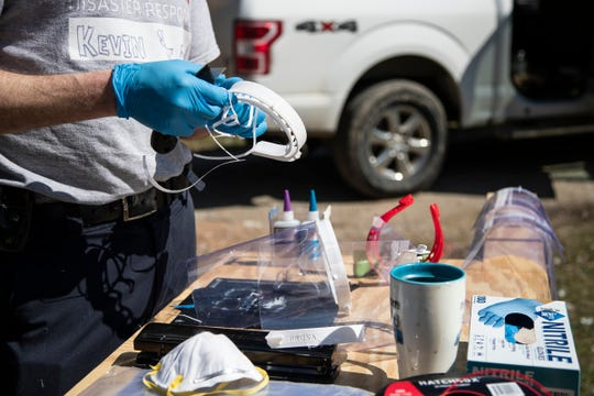 Kevin Leeser of Ann Arbor scrapes off the excessive plastic from the 3D printed face shield at his home in Ann Arbor on March 25, 2020.