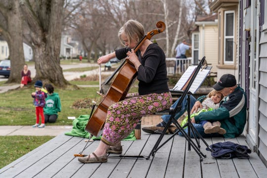 Irina Tikhonova plays the cello on her front porch on Thursday in Royal Oak for neighbors and people passing by as husband Fred Trimble holds their 4-year-old granddaughter Mia.