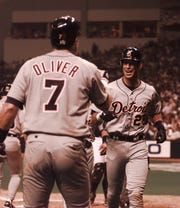 Tigers left fielder Luis  Gonzalez is all smiles as he gets a hand from Joe Oliver, after scoring one of the Tigers' early runs during their 1998 season opener against the Tampa Bay Devil Rays on March 31, 1998.