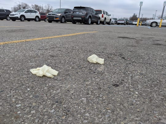 A pair of discarded rubber gloves lies on the pavement of the Walmart Supercenter parking lot on North Pontiac Trail in Commerce Township, Michigan in this March 26, 2020 photo. South Jersey towns are having the same issue.