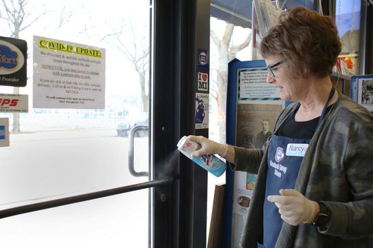 Nancy Strang, attendant at Central Drug Store in downtown Charlevoix, disinfects the door handles and checkout kiosk after each customer enters and leaves the store. The  pharmacy is one of the only shops open downtown during the state-wide shutdown of non-essential services.