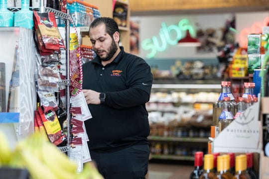 Owner Kyle Shammami arranges a shelf at Penny Lake Market in Walled Lake, Wednesday, March 25, 2020.