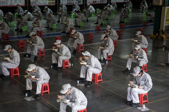 Employees eat their lunch while staying 2 meters away from each other at the Dongfeng Fengshen plant on March 24, 2020 in Wuhan, Hubei province, China. Wuhan has allowed car producers and auto part suppliers to resume work recently. The Dongfeng Passenger Vehicle Company has resumed production following epidemic prevention and control rules. Local media have reported that Wuhan will lift the lockdown on April 8.