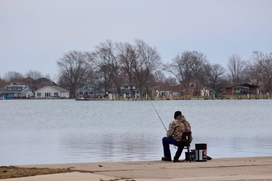 A man sits in his chair in hopes of catching a fish at Black Creek on Thursday, March 26, 2020, at Lake St. Clair Metropark in Harrison Township.