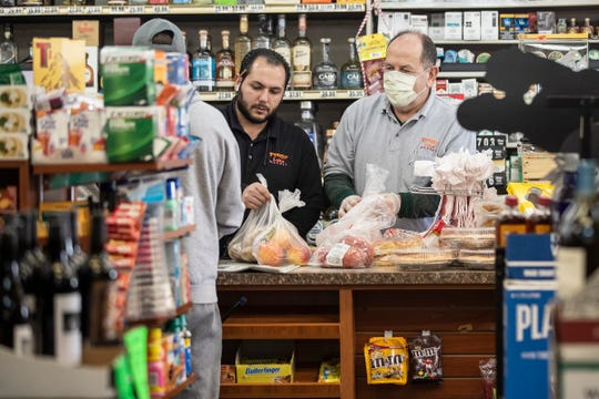 Kyle Shammami and his father Mark bag groceries for a customer at the Penny Lake Market in Walled Lake, Wednesday, March 25, 2020.