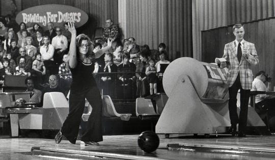 Host Bob Allison (at right) and contestant Laura Taylor from the 'Bowling For Dollars' television show.
