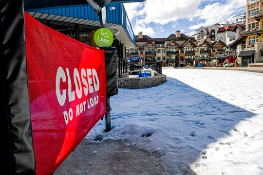 In this Tuesday, March 24, 2020, photo a sign hangs on a closed ski lift in Vail, Colo., after Vail Ski Resort closed for the season amid the COVID-19 pandemic.