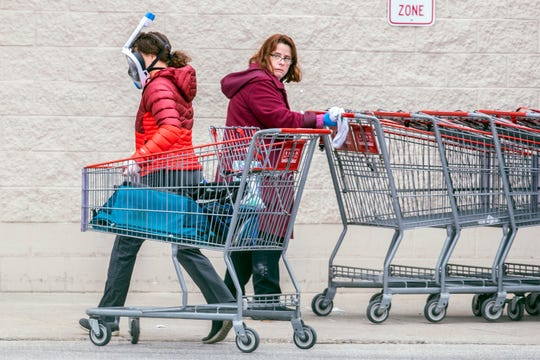 A Costco employee, right, looks toward a shopper wearing a mask and snorkel to go shopping, as she sanitizes carts that are returned from the parking lot to help reduce the spread of coronavirus Wednesday in King of Prussia, Pennsylvania.