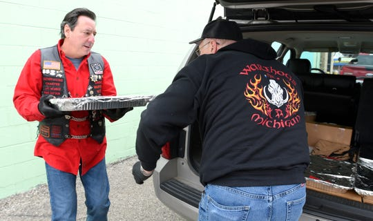 Joe 'Chooch' Sciortino, left, brings a tray of food to club member Bob 'Uber' Hagberg before they deliver to Metro Detroit area emergency rooms, Thursday, March 26, 2020.