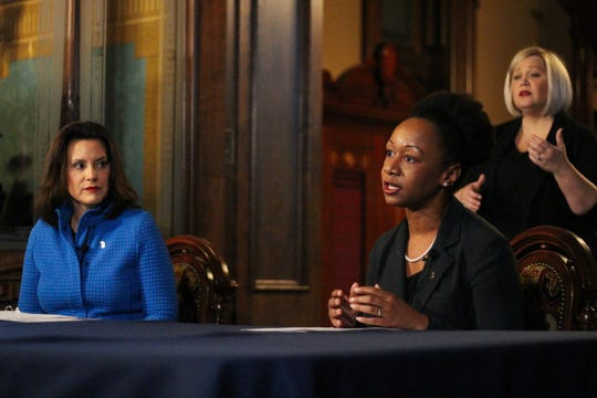 Dr. Joneigh Khaldun, right, chief medical executive and chief deputy director for health for the Michigan Department of Health and Human Services, speaks during a press conference in Lansing as Gov. Gretchen Whitmer listens.