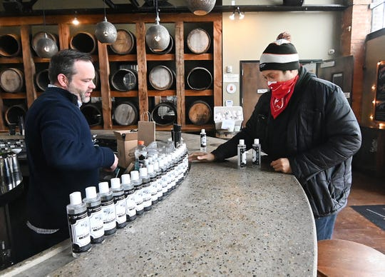 Sean McCarthy (left), bartender, manager, gives an eight-ounce bottle of hand sanitizer to Ethan Johnson as the Two James distillery in Detroit has converted their liquor production to making alcohol-based hand sanitizer.