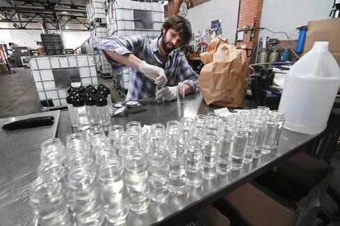 Ben Senseney, taste room manager, caps and labels 8 ounce bottles of alcohol-based hand sanitizer in Detroit on Thursday, March 26, 2020. The Two James distillery have converted their liquor production to making hand sanitizer.