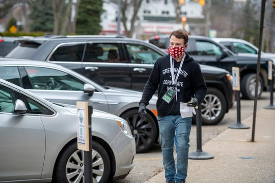 Employee Jarred Brooks brings an order to a driver waiting curbside on Walled Lake Road at The Greenhouse marijuana dispensary in Walled Lake.