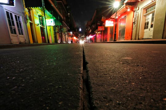 In this Thursday, March 19, 2020, file photo, a view of the nearly deserted scene on Bourbon Street, which is normally bustling with tourists and revelers, in the French Quarter of New Orleans.