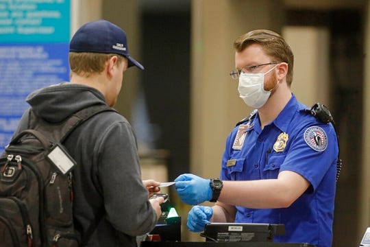 A traveler goes through security at the Salt Lake City International Airport Wednesday. a Utah county hard hit by the new coronavirus is telling residents to stay home except for essential errands and asking visitors to the ski-resort community of Park City to stay away.
