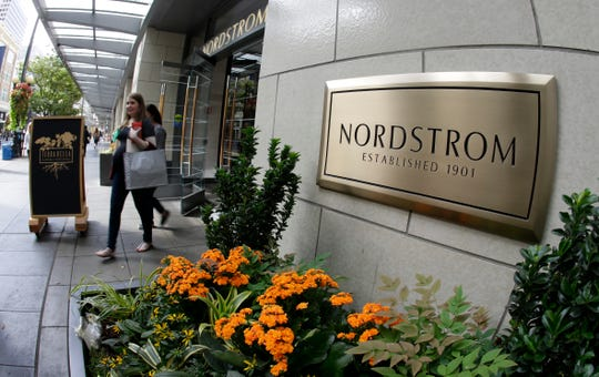 In this Wednesday, Sept. 13, 2017, photo, shoppers come and go from Nordstrom's flagship store in downtown Seattle. Nordstrom will start to furlough a portion of its corporate employees starting April 5 for six weeks.