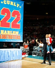 "In this Feb. 15, 2008, file photo, Harlem Globetrotters' Fred ""Curly"" Neal looks on with his grandson Jaden Neal-Roberts as his No. 22 is retired by the world renowned Harlem Globetrotters at Madison Square Garden in New York."