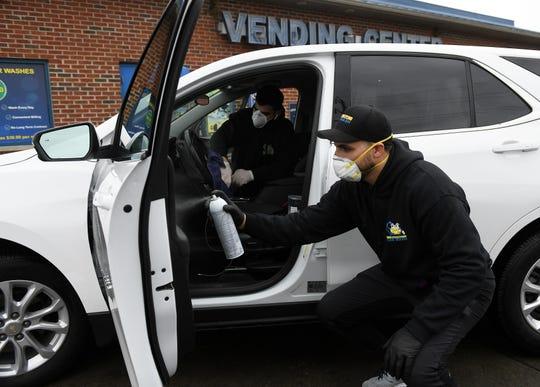 Co-owner Alex Issa, 29, right, sanitizes the interior of a doctor's car with Ahmad Ahmad, 21, at Magical Touch Car Wash in Detroit. Magical Touch is offering a free car wash and interior sanitizing to all first responders, health care workers, grocery workers, basically any critical infrastructure workers that are still on the job during the COVID-19 pandemic.
