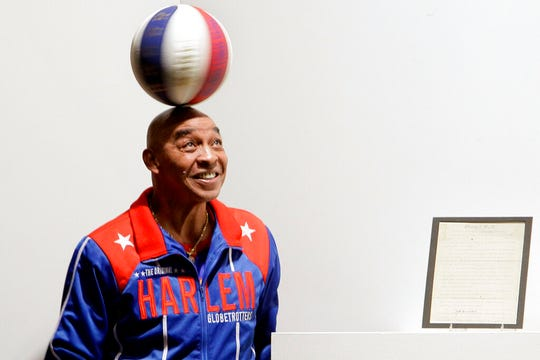 "In this Dec. 10, 2010, file photo, Harlem Globetrotters Fred ""Curly"" Neal spins a ball on his head prior to the bidding for the Naismith Rules, the original rules for basketball, framed at right, at Sotheby's in New York. Neal, the dribbling wizard who entertained millions with the Harlem Globetrotters for parts of three decades, has died the Globetrotters announced Thursday, March 26, 2020. He was 77."