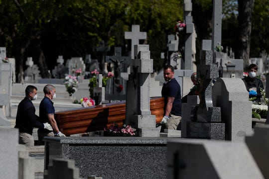 Pallbearers carry a coffin of a person who died of coronavirus at the cemetery of La Almudena in Madrid, Spain, Thursday.