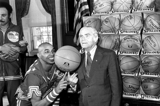 "In this Feb. 15, 1977, file photo, the Harlem Globetrotters' Fred ""Curly"" Neal of shows New York City Mayor Abe Beame the art of balancing a basketball on a finger during ceremony at City Hall."