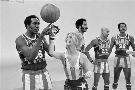 Actress Goldie Hawn has her finger guided to the basketball by Harlem Globetrotters' Meadowlark Lemon during the taping of her CBS special in Burbank, Calif., Feb. 2, 1978. In background center is Curly Neal. Other Globetrotters are unidentified.