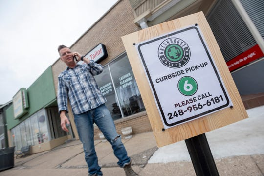 Jerry Miller, owner of The Greenhouse marijuana dispensary in Walled Lake, takes a call near designated pick-up parking spaces on Walled Lake Road, March 26, 2020.  A stay-home edict by Gov. Gretchen Whitmer limited marijuana sales to deliveries and curbside pickup.