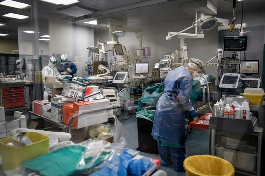 In this photograph taken from behind a window, doctors inside a Covid-19 intensive care unit of San Matteo Hospital, in Pavia, northern Italy, Thursday. The San Matteo hospital is where Patient 1, a 38-year-old Unilever worker named Mattia, was kept since he tested positive for Covid-19 on Feb. 21 and opened Italy's health care crisis.