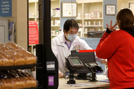 A pharmacist, left, assists a customer while working behind a plastic shield at a grocery store, Thursday, March 26, 2020, in Quincy, Mass. Grocery stores across the U.S. are installing protective plastic shields at checkouts to help keep cashiers and shoppers from infecting each other with the coronavirus.