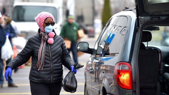 Darleen McCoy, of Detroit, puts a bag of food in the rear of a vehicle at Zaman's Hope for Humanity Center, Thursday, March 26, 2020.