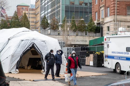 Medical Examiner personnel and construction workers are seen at the site of a makeshift morgue being built in New York, Wednesday, March 25, 2020.