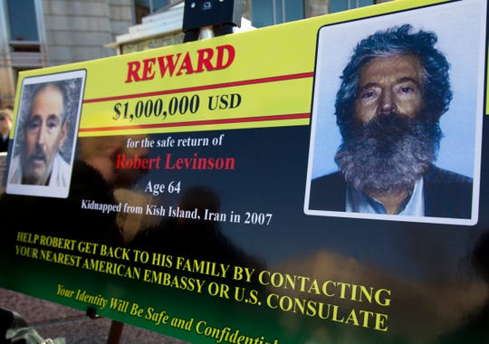 FILE - In this March 6, 2012 file photo, an FBI poster showing a composite image of former FBI agent Robert Levinson, right, of how he would look like now, left, taken from the video, released by his captors in Washington during a news conference.