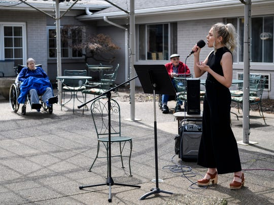 Kaitlyn Madison of Haubstadt sings to residents in the courtyard of Heritage Center & Horizons Rehabilitation as the temperature hit the mid-70s in Evansville, Thursday afternoon, March 26, 2020. A few residents were wheeled outside and placed over six-feet from one another while others listened to Madison through their open windows.