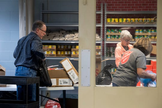 Volunteers Bill Fenet, left, Susan Wood, center, and Chris Kuryla, right, work in the food pantry at the Salvation Army in Evansville, Ind., Wednesday afternoon, March 25, 2020. The food pantry is open 1-3 p.m. Monday, Wednesday and Friday.